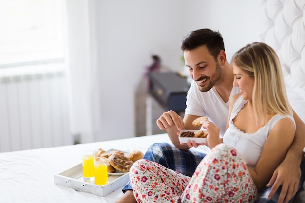 Young happy couple having having romantic times in bedroom