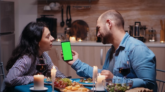 Young happy couple holding green screen phone at dinner. cheerful people looking at mockup template chroma key isolated smart phone display using techology internet sitting at the table in kitchen.