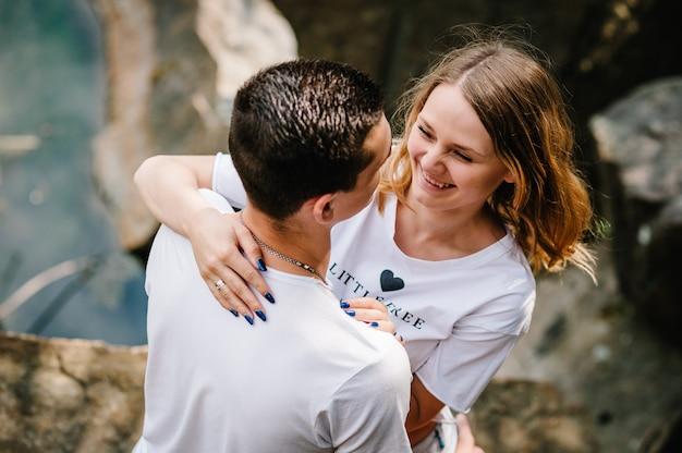 Молодая счастливая пара обнимается на камне у озера