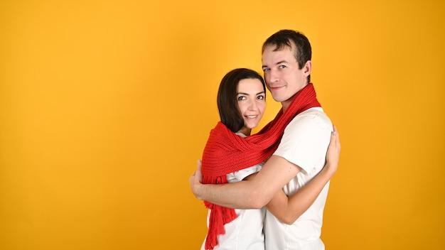 Молодая счастливая пара обнимает друг друга на желтом