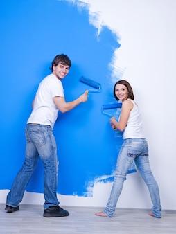 Молодая счастливая пара в повседневной одежде, чистящая стену