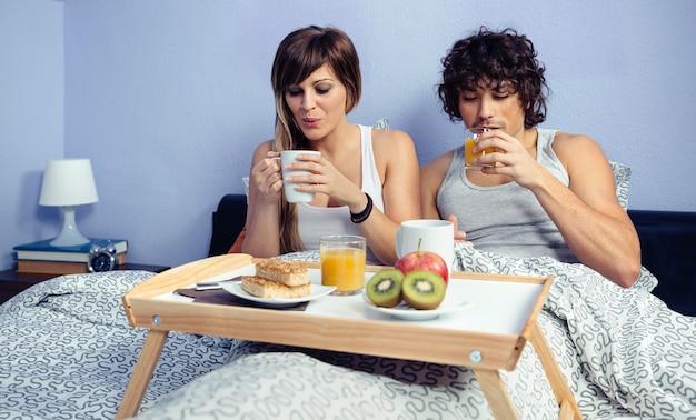 Молодая счастливая пара в любви, завтракающая в постели, подается на подносе у себя дома. концепция домашнего образа жизни пара.