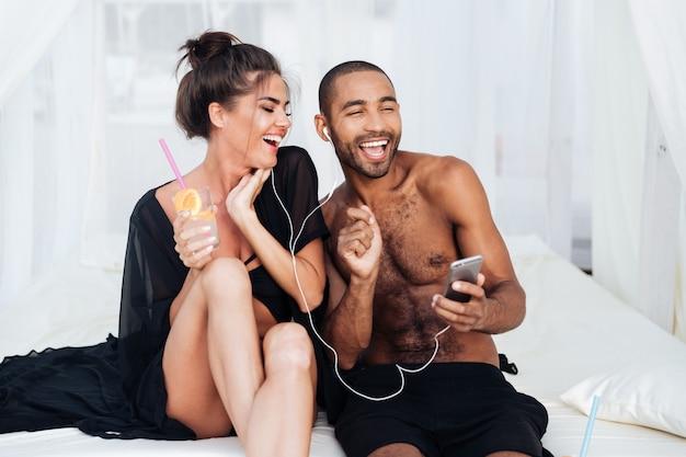 イヤホンで音楽を聴きながらビーチで楽しんで愛の若い幸せなカップル