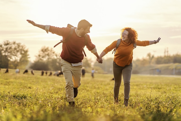 Молодая счастливая пара в любви, взявшись за руки и бегая по природе. прекрасный солнечный осенний день. свобода.