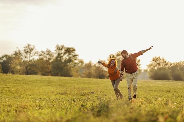 手をつないで牧草地で走るのが大好きな若い幸せなカップル。それは美しい晴れた秋の日です。
