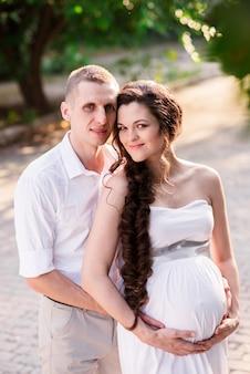 屋外で恋をしている若い幸せなカップル。公園で愛する男と妊婦。