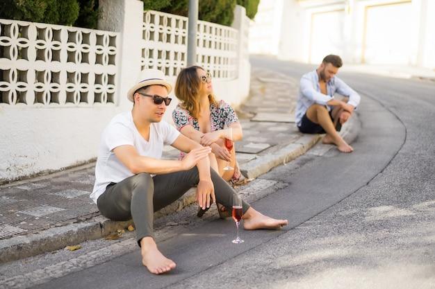 愛の若い幸せなカップルはスペインの小さな通りを歩き、シャンパンを飲み、笑います。休暇