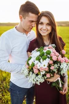 Молодая счастливая пара в любви, женщина держит цветы, счастливы и наслаждаются обществом друг друга