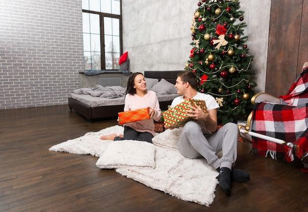パジャマを着た若い幸せなカップルは、ロフトスタイルの部屋のクリスマスツリーの近くのカーペットに座ってプレゼントを喜んでいます