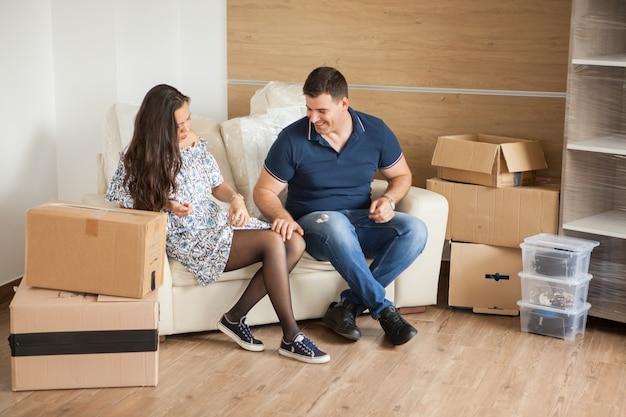 新しい家で移動ボックスと部屋で若い幸せなカップル。彼らの新しい家での幸せ