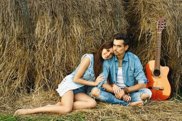 干し草の山の中で村の若い幸せなカップル。
