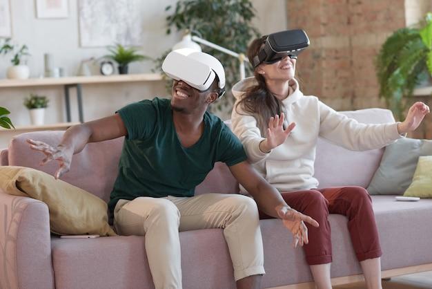 ソファに座って一緒にビデオゲームをプレイするバーチャルリアリティメガネの若い幸せなカップル