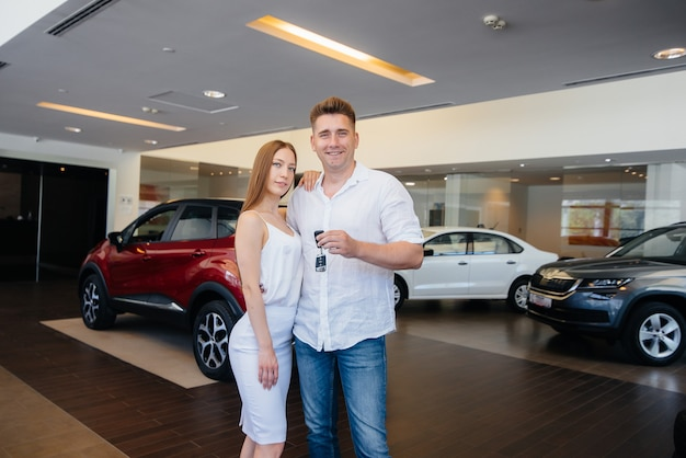 A young happy couple is happy to buy a new car. car purchase.