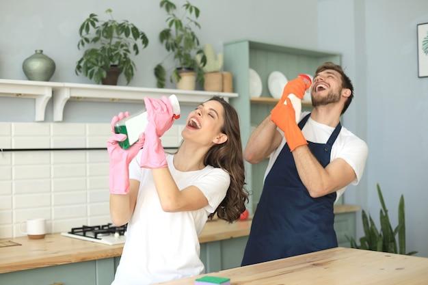 若い幸せなカップルは家で掃除をしながら楽しんでいます。