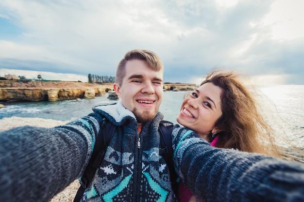 若い幸せなカップルは、海の近くで休暇中に自分撮り写真を撮っています。