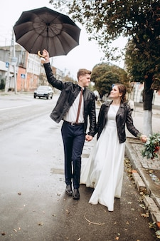 Young happy couple is walking on a city street after rain. close-up portrait of a man and woman with an umbrella. loving couple smiling outdoors. a man walks down the street and waving an umbrella