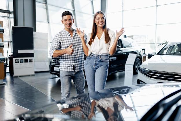 Молодая счастливая пара только что купила новую машину в автосалоне
