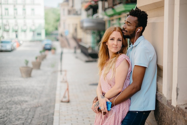 Young happy couple listening to music together with earphones on a city street on a sunny day