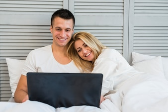 Young happy couple looking at laptop with blanket on bed