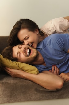 Young and happy couple lying on a sofa