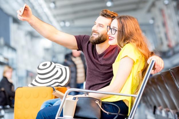 젊은 행복한 커플은 여름 방학 동안 공항 대기실에서 전화로 셀카 사진을 찍는다