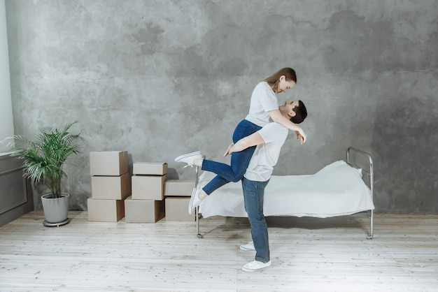 Young happy couple man and woman in room with moving boxes in new home