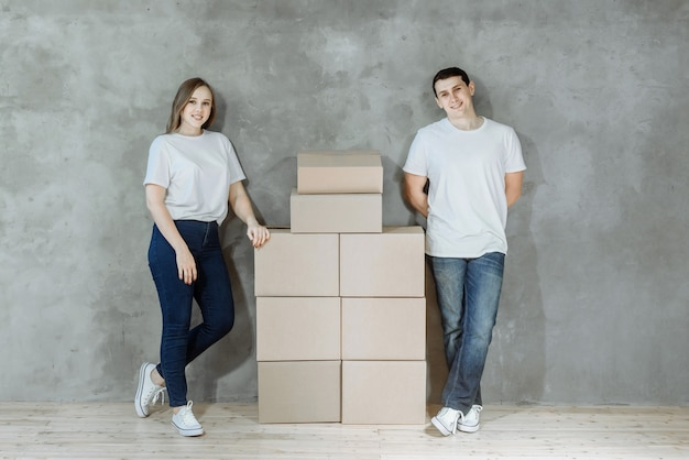Young happy couple man and woman standing on the background of a wall in a new house among cardboard boxes for moving