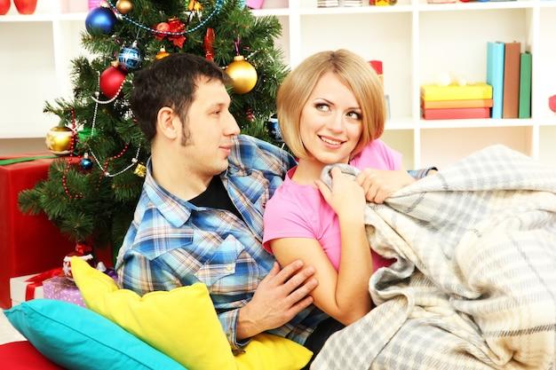 自宅のクリスマスツリーの近くの若い幸せなカップル