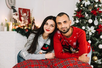 Young happy couple near Christmas tree
