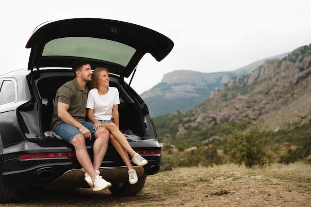 Молодая счастливая пара в поездке, сидя в багажнике автомобиля