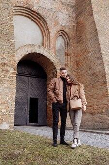古い市壁に若い幸せなカップル。旧市街の中庭で散歩を楽しむ愛のカップル。壁に、赤レンガの壁。セレクティブフォーカス