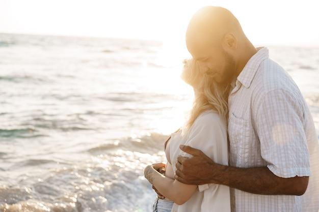 바다를 즐기는 해변에서 젊은 행복한 커플을 닫습니다