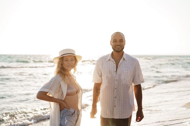海を楽しむ海岸の若い幸せなカップル