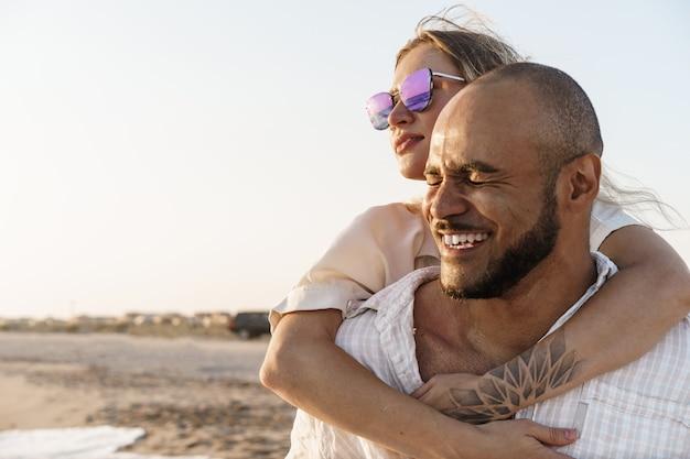 바다를 즐기는 해변에서 젊은 행복 한 커플