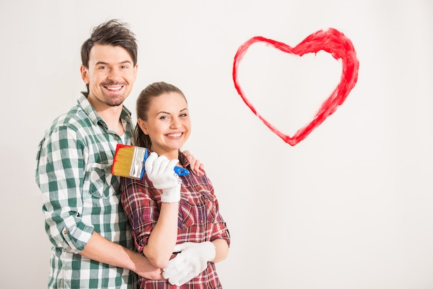Молодая счастливая пара нарисовала сердце на стене.