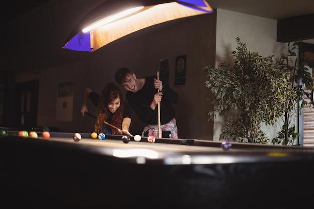 Молодая счастливая пара играет в бильярд