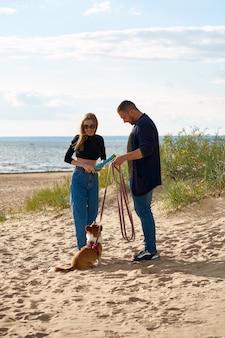 Молодая счастливая пара играет с собакой