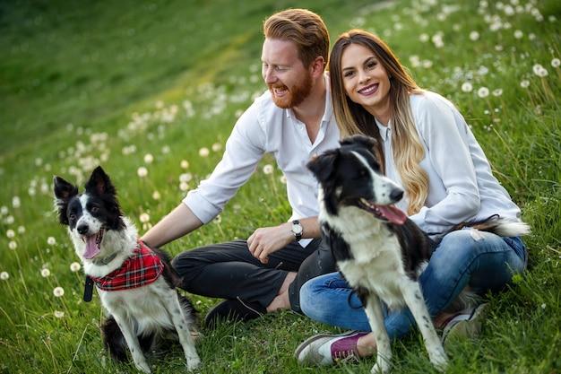 Молодая счастливая пара играет с собаками, развлекаясь в парке на открытом воздухе