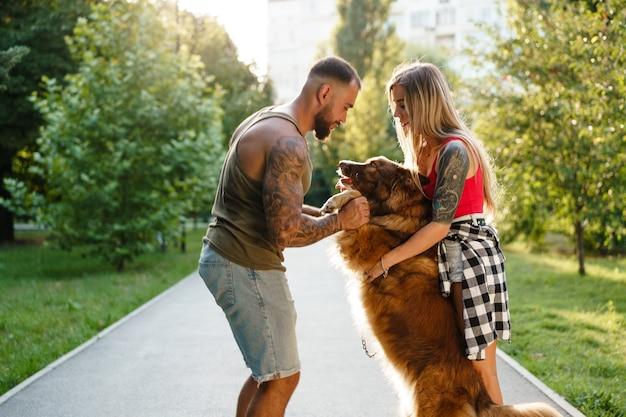 Молодая счастливая пара играет со своей собакой, улыбаясь в парке