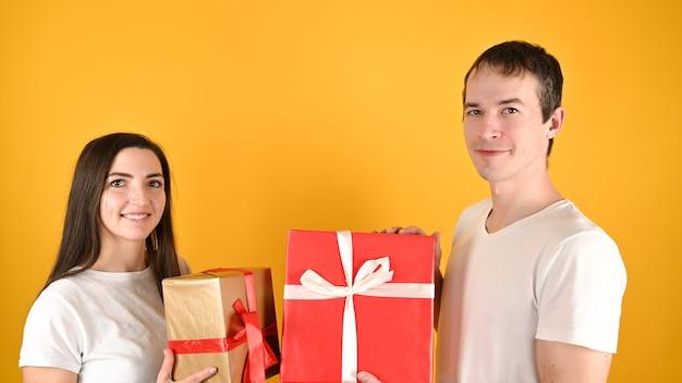 Молодая счастливая пара получила подарки друг от друга на желтом