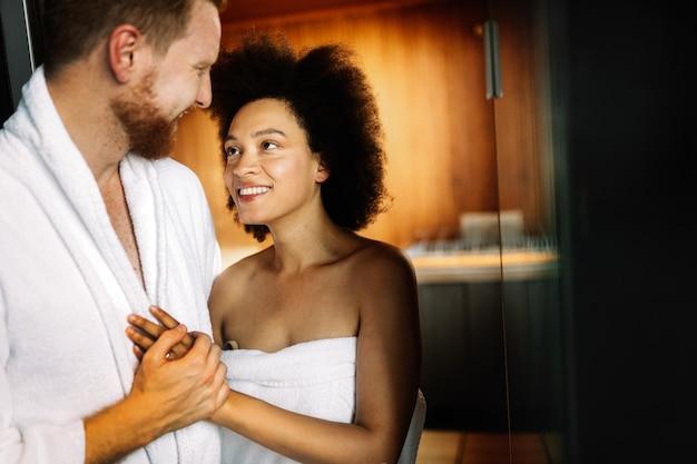 Молодая пара счастлива расслабляющий в сауне в роскошном спа-отеле курорта. романтические влюбленные проводят день ухода за телом в паровой бане