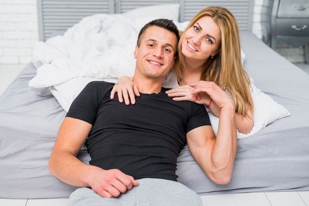 Young happy couple resting in bedroom