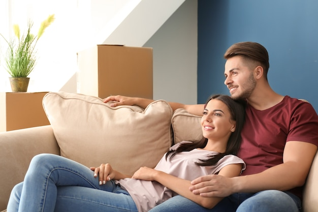 Молодая счастливая пара, отдыхая на диване в новом доме