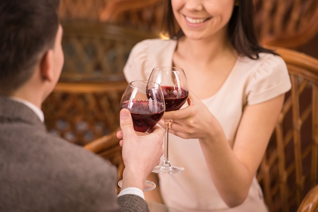 Young happy couple romantic date drink glass of red wine.