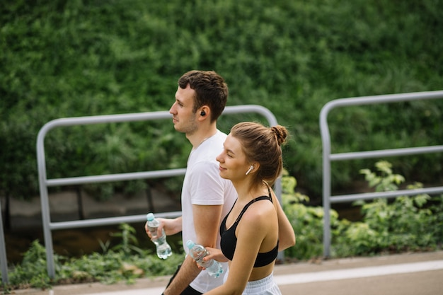 Young happy couple running in city park with botle of water in hands, joint sports, cheerfulness, city sport healthy lifestyle, fitness together at summer evening, runners