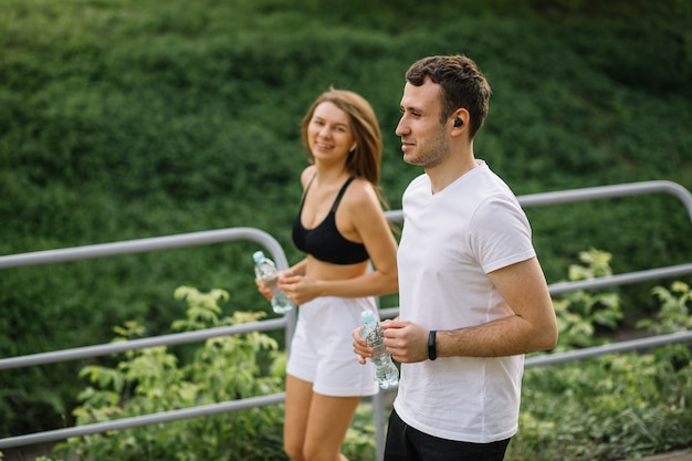 Young happy couple running in city park with botle of water in hands, joint sports, cheerfulness, city sport healthy lifestyle