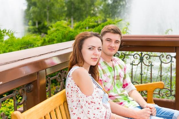 분수와 다른 나무를 배경으로 공원 벤치에 앉아 있는 젊은 행복한 커플