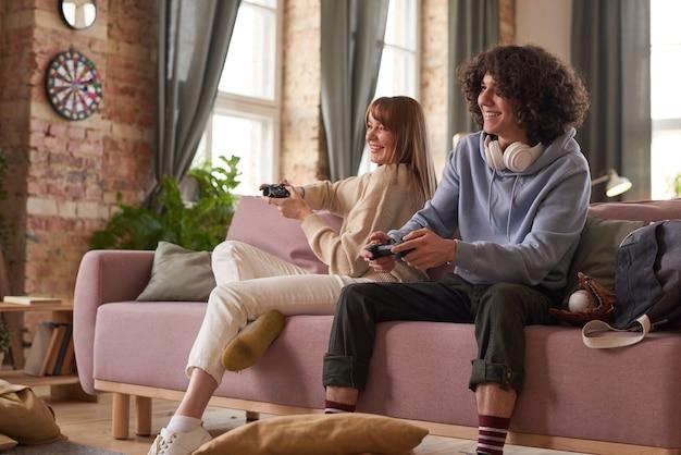 ソファに座って、リビングルームでコンピューターのビデオゲームを楽しんでいる若い幸せなカップル