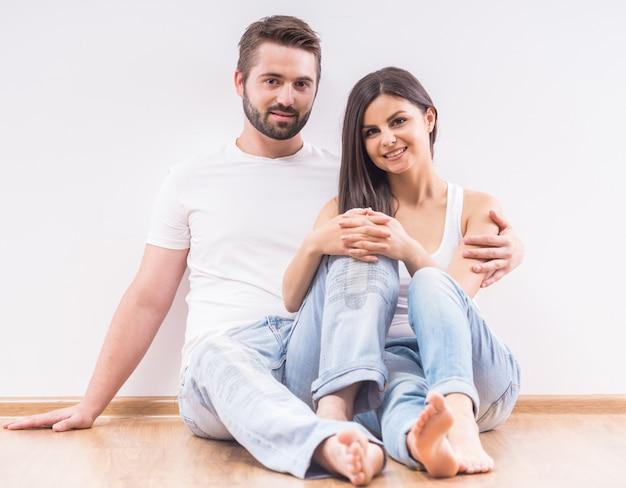 移動後の自宅の床に座っている若い幸せなカップル。