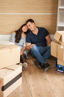 開梱後に休んで床に座っている若い幸せなカップル。箱を運んだ後のカップルの冷え